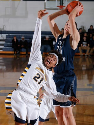 East Lansing's Brandon Johns, right, grabs a rebound over Grand Ledge's Malek Adams Tuesday, Feb. 24, 2015, in Grand Ledge, Mich.