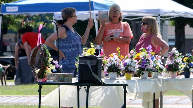 Renae Hughart, from left, Lesa Suttles and Tammy Hanna pass the time chatting, Saturday, June 6, 2020, on the Greenwood Square during the first day of the Greenwood Farmers Market.