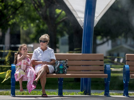 Brynn Rubin, 5, takes a break from the splash pad to have popcorn on a bench with her grandmother, Michele Theisen, of Port Huron, Thursday, June 2, 2016 at Lakeside Park in Port Huron. The city is looking at ways to handle increasing crowds after nearly 7,000 people filled the park on Memorial Day.