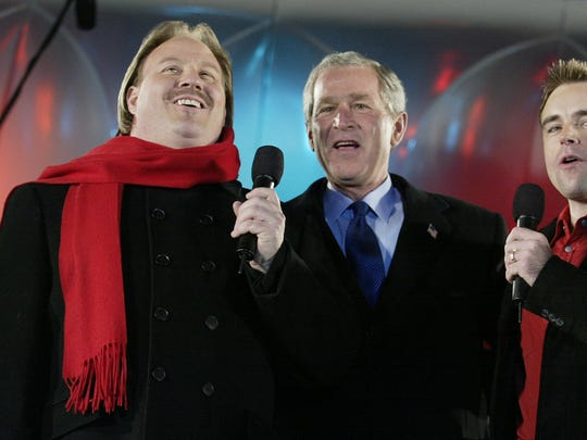 President George W. Bush (C) sings Christmas songs with tenor Carl Tanner (left) and performer Darren Holden on Dec., 2004, at the annual Pageant of Peace on The Ellipse behind the White House in Washington, DC.