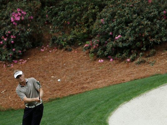 FILE - In this Wednesday, April 5, 2017 file photo, Bernhard Langer of Germany hits on the 13th hole during a practice round for the Masters golf tournament in Augusta, Ga. Augusta National's colorful, blooming azaleas are mostly missing this Masters, victims of a warmer than usual winter and sudden March cold snap. The bursts of pink and white are as much a part of the tournament as Magnolia Lane and the champion's green jacket. This time, though, the flowering plants and shrubs could not survive the confluence of strange weather, leaving TV viewers, competitors and patrons longing for the vibrant display. (AP Photo/Matt Slocum, File)
