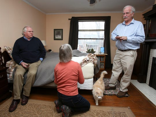 Russ Barnett, right, director of the Kentucky Institute for the Environment and Sustainable Development at the University of Louisville, spoke with Courier-Journal environmental reporter James Bruggers, left, and his wife Christine Bruggers in their bedroom.  He was testing the air quality in their home.