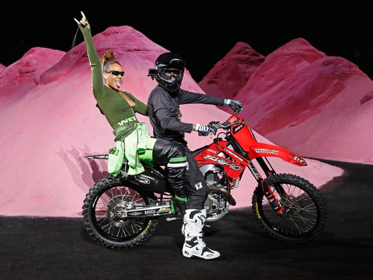 Rihanna rides a dirtbike on the runway at the FENTY