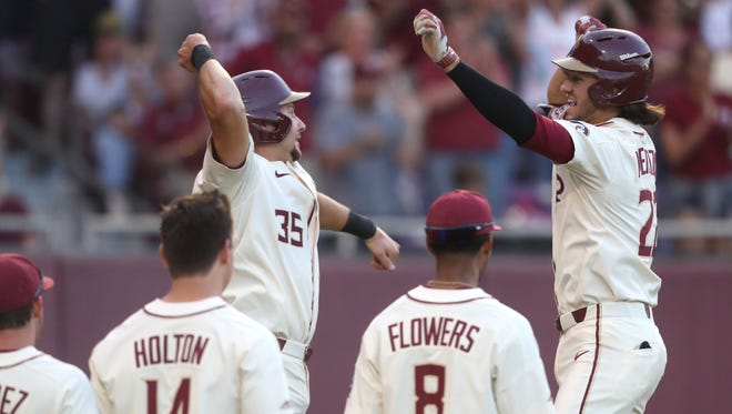 FSU's Cal Raleigh, left, greets Drew Mendoza at home plate to celebrate his 2-run home run against Miami during the Seminole's 10-1 win over the Hurricanes at Dick Howser Stadium in Tallahassee, Fla. on Saturday, April 28, 2018.