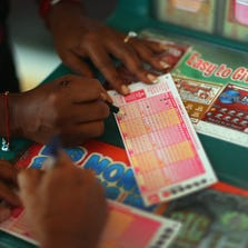 Woman fills out her Powerball numbers as she buys a ticket at Circle News Stand