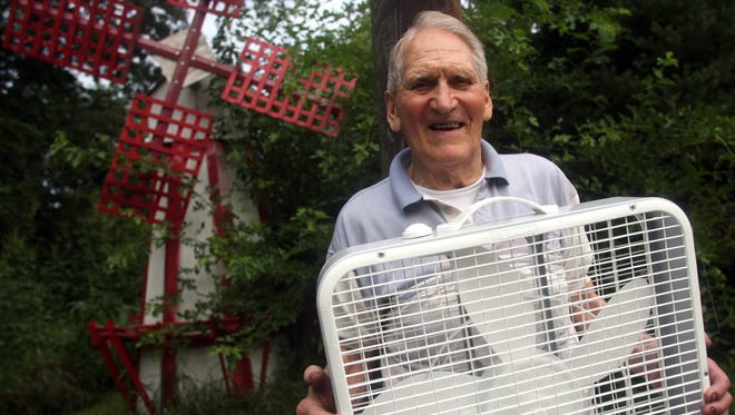 [File Photo]  Joe Hoard holds a box fan, one of many that he donates to the Crisis Center every year, on his property outside Hills, Iowa Wednesday August 15, 2007.