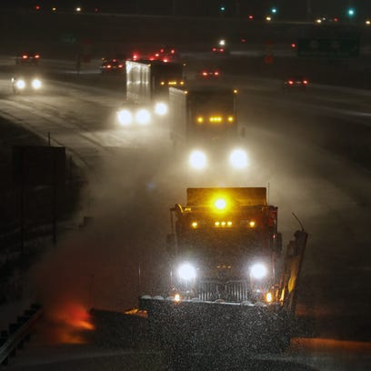 A snowplow clears snow in the northbound lane of Interstate