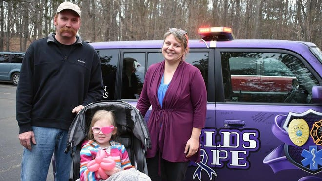 Saugatuck Firefighter Capt. Mike Betts and AMR Paramedic Melissa Betts stand with their daughter, Avery. Avery died from an aggressive form of brain cancer called DIPG at the age of 7.