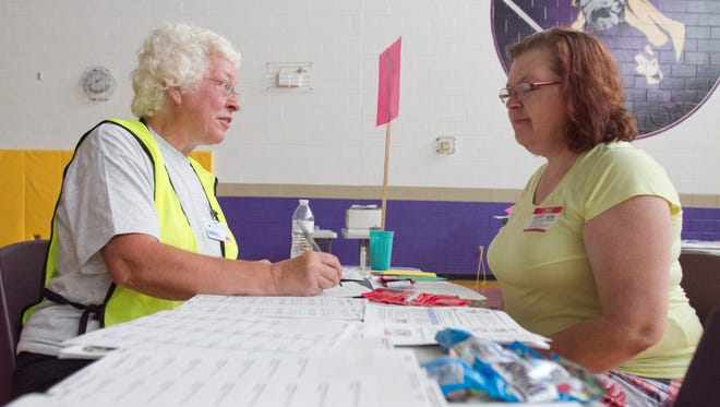 At left, Joan Wirkner, R.N. checks the criteria for determining 'dosage' of an antidote for anthrax for volunteer Mary Hogg in a mock drill held at Fowlerville High School. In this exercise, 'patients' are given Skittles candies and Welch's Fruit Snacks to represent the medicine prescribed.