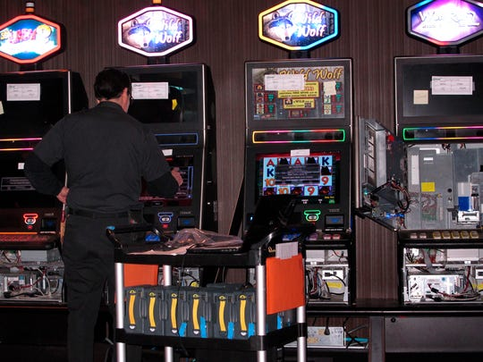 A technician installs slot machines on the casino floor