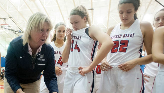 Sacred Heart head basketball coach Donna Moir talks to her players during a time-out.