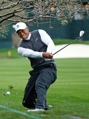 Tiger Woods hits the ball from under a tree on the 11th hole during the second round of the Waste Management Phoenix Open at TPC Scottsdale.