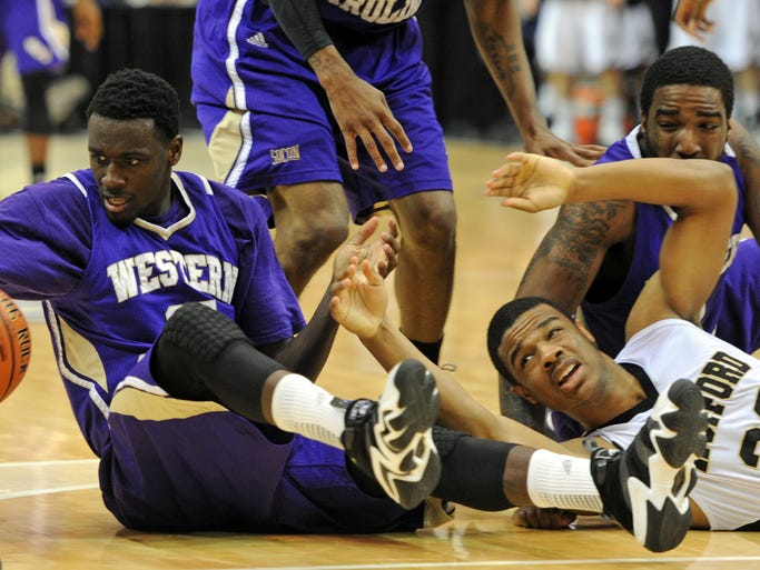 WCU's James Sinclair (25), Trey Sumler (5), and Kenneth Hall (1) scramble to keep the ball from Wofford's Spencer Collins (32) during their game Monday.  In a close game until the end, Wofford beat Western Carolina University 56-53 in the finals of the Southern Conference tournament championship Monday night at the U.S. Cellular Center. 3/10/14 - Erin Brethauer (ebrethau@citizen-times.com)