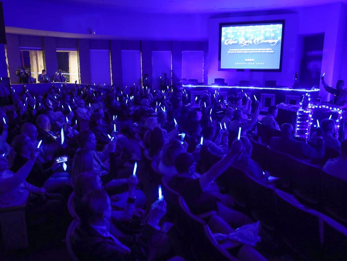 Attendees holds lights during the Blue Light Ceremony