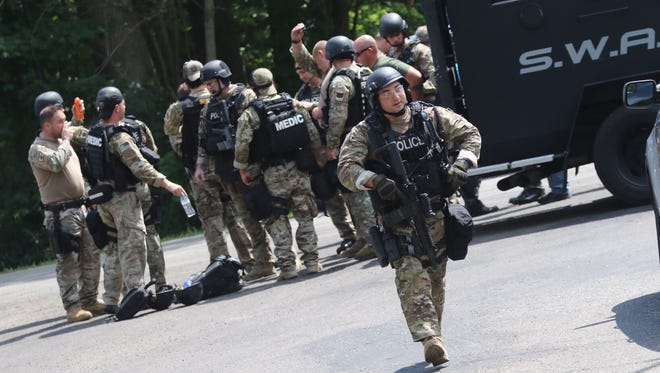 The SWAT team assembles at Rummel and Mansfield-Lucas roads on Wednesday afternoon.