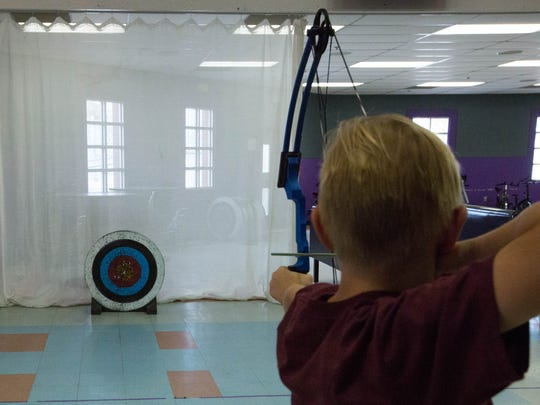 Jaeton Monroe, 10,, demonstrate his archery skills in the Camino Real Middle School Cafeteria, Thursday April 19, 2018.