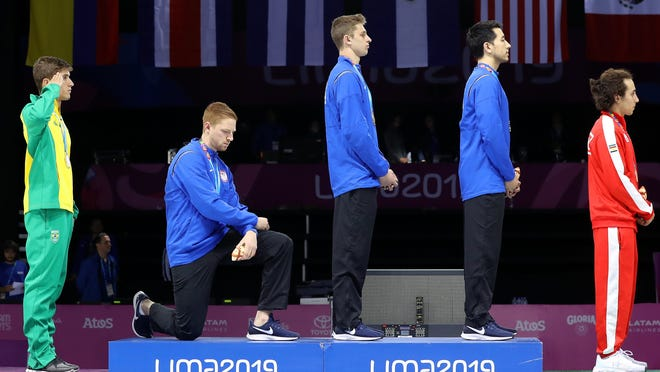 LIMA, PERU - AUGUST 09: Gold medalist Race Imboden of United States  takes a knee during the National Anthem Ceremony in the podium of Fencing Men's Foil Team Gold Medal Match Match on Day 14 of Lima 2019 Pan American Games at Fencing Pavilion of Lima Convention Center on August 09, 2019 in Lima, Peru. (Photo by Leonardo Fernandez/Getty Images) ORG XMIT: 775311501 ORIG FILE ID: 1167100210