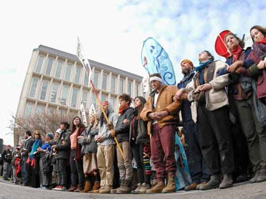 Dakota Pipeline protesters stand arm-in-arm at the intersection of Rosser Avenue and Fourth Street in downtown Bismarck, N.D., after marching from the state Capitol to the William L. Guy Federal Building, Monday, Nov. 14, 2016.