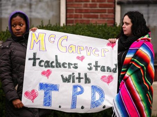 """Erika Edwards, left, and Michelle Pigott, teachers at McCarver Elementary School, hold a sign of support during the procession for Tacoma police Officer Reginald """"Jake"""" Gutierrez on Friday, Dec. 2, 2016 in Tacoma, Wash. Crowds gathered to pay respects to Gutierrez who died Wednesday after being shot while responding to a domestic violence call."""