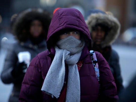 Morning commuters bundle up, Thursday, Dec. 15, 2016, in Chicago. Dangerously cold temperatures gripped the Upper Midwest in advance of a storm that's expected to bring several inches of snow in coming days.