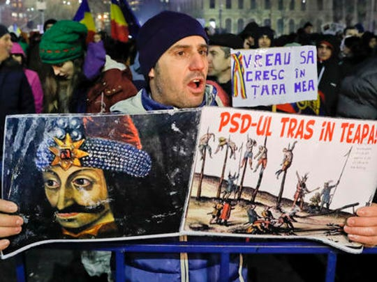 "A man holds a poster that reads ""The Social Democracy Party (PSD) - Impaled"" near a depiction of Romanian medieval ruler Vlad the Impaler, during a protest joint by thousands against a government decree that dilutes what qualifies as corruption, in Bucharest, Romania, Thursday, Feb. 2, 2017. Huge protests erupted in the capital and spread to cities around Romania in the past two nights after the government changed the law — one of the biggest protests in Romania since communism ended in 1989."