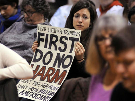 Amy Kuiken, 34, of Dallas, Pa., holds her sign, as she listens to a person's story during a town hall meeting regarding health care at the United Neighborhood Center in Scranton, Pa., Tuesday, Feb. 21, 2017. Sen. Pat Toomey, R-Pa., was invited to speak at the town hall, but did not attend.