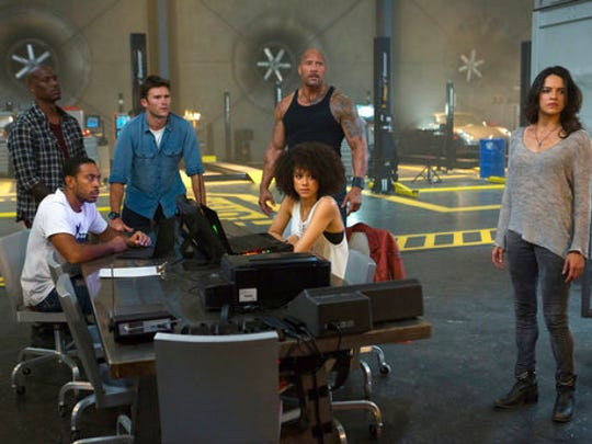 "This image released by Universal Pictures shows, Chris ""Ludacris"" Bridges, seated left, and Nathalie Emmanuel, seated right, and Tyrese Gibson, standing from left, Scott Eastwood, Dwayne Johnson and Michelle Rodriguez in ""The Fate of the Furious."""