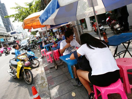 In this April 7, 2017 photo, people eat noodles at a street food shop during their lunch on Thonglor road in Bangkok, Thailand. Officials see street food as an illegal nuisance and have warned hawkers in Thonglor to clear out by April 17. Efforts by authorities in military-ruled Thailand to impose order on the chaotic capital city have a fresh target: cheap and tasty pad thai. The latest crackdown by Bangkok city officials is going after the vendors whose carts selling everything from Thailand's signature noodles to spicy tom yum goong soup have become institutions on the capital's hot and humid sidewalks.