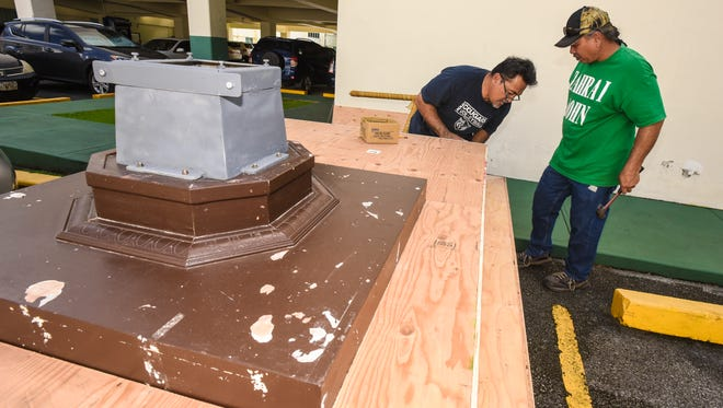 Volunteers Vic Santiago, left, and Jess Castro, work together to construct a karosa cart in Hagåtña on Tuesday, Dec. 6, 2016. The cart will be decorated and used to parade the Santa Marian Kamalen statue in a procession through downtown Hagåtña during the Feast of the Immaculate Conception, celebrated annually on Guam on Dec. 8.