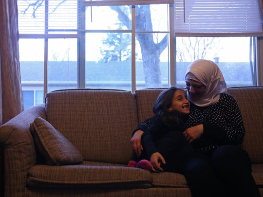 Hala Tameem, 6, sits on the couch with her mother, Ghazweh Aljabooli, 35, in their Des Moines apartment, on Tuesday, Nov. 15, 2016. The Tameem family were the first Syrian refugees to come to Des Moines in June.