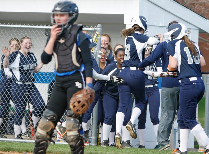 Mercy's MiKayla Schlehr, 9, back center, jumps into the arms of her teammates after scoring the lone run of the game in the seventh inning as Brockport catcher Shelby Perry regroups at the plate.