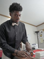 William Murphy cuts fabric for bow ties, working in