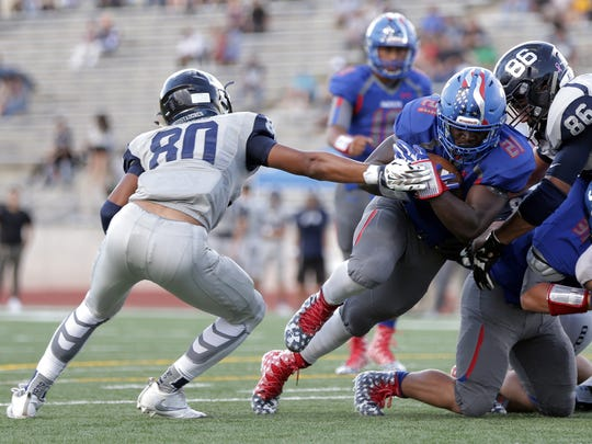 Americas running back Josh Fields breaks past Del Valle's Nicholas Sparks on his way to over 170 yards in his season opener Thursday at the Socorro Student Activities Complex.