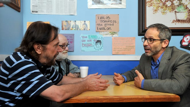 Wraps owner Yianni Allis (left) talks with Rabbi Ted Riter of Beth Israel Congregation as friend of Allis, Richard Sneed of Jackson (back) looks on Friday at the restaurant in Jackson. The two had a sit down to work out their differences after a an uncomfortable situation at the restaurant on Tuesday.