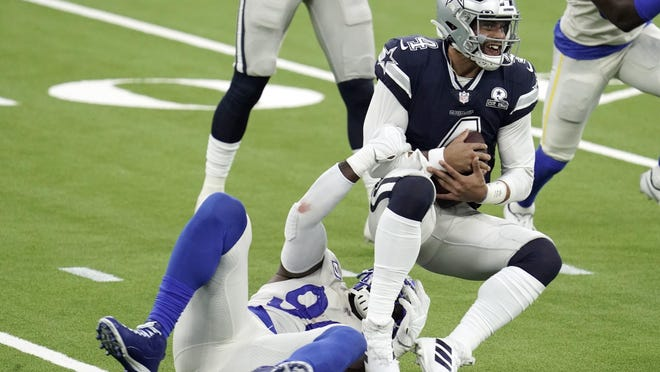 Dallas Cowboys quarterback Dak Prescott, right, is tackled by Los Angeles Rams defensive end Michael Brockers during the first half of an NFL game Sunday, in Inglewood, Calif.