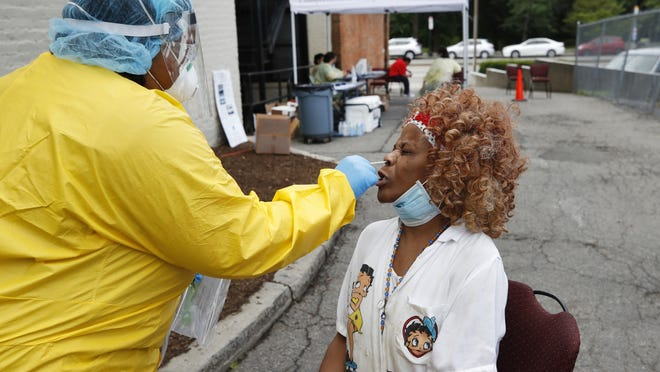 FILE - Leanora Rodriguez receives a COVID-19 test from Nurse Meiko Rollins at the Whittier Street Health Center's mobile test site, Wednesday, July 15, 2020, in Boston's Dorchester section.