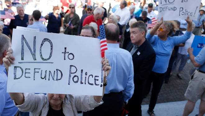 """Demonstrators opposed to """"defund the police"""" movements on the steps of Athens-Clarke County City Hall before a commission meeting on the annual budget, where commissioners Mariah Parker and Tim Denson proposed their 50/10 plan in Athens, Ga, on Tuesday, June 16, 2020."""