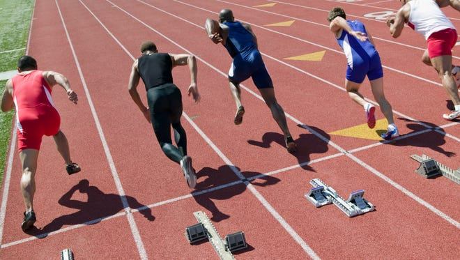 Male sprinters leaving starting blocks in a track-and-field meet.