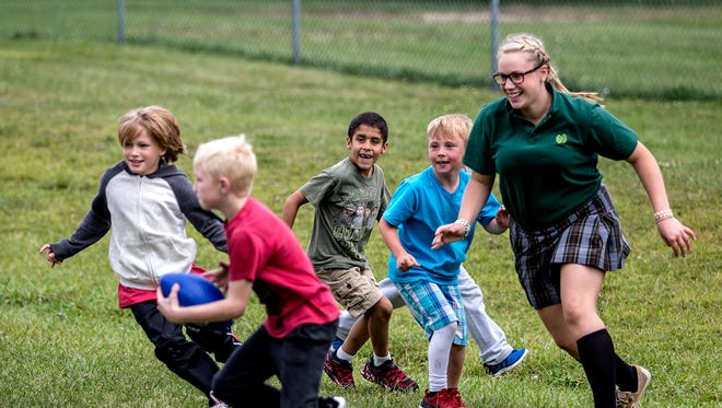 Bailee McKenzie, a senior at Newark Catholic, chases students from McGuffey Elementary during a game of football she helped organize during recess time.