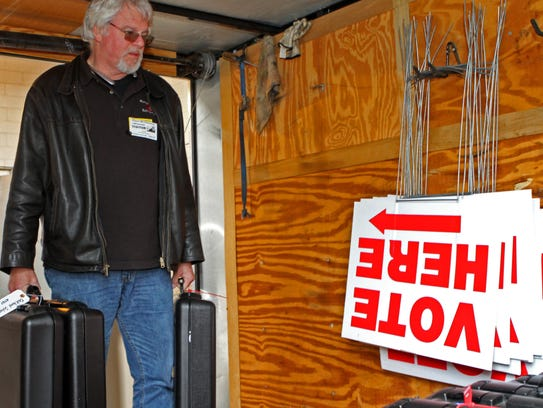 Jeff Broome carries voting machines into a trailer