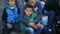 A Honduran mother holds her son, 7, after she turned