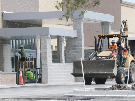 Crews work on the construction of the new Wal-Mart of San Carlos Boulevard near Summerlin Road on Friday. There are several properties adjacent to the new Wal-Mart that are unoccupied.