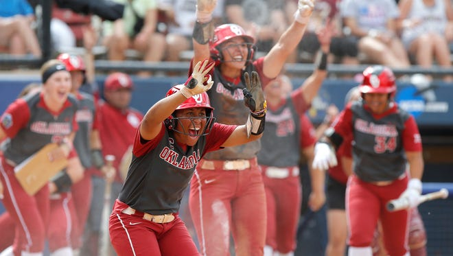 Oklahoma's Nicole Mendes and Kelsey Arnold after the Sooners scored a run against Oreogn during the fifth inning at the Women's College World Series.