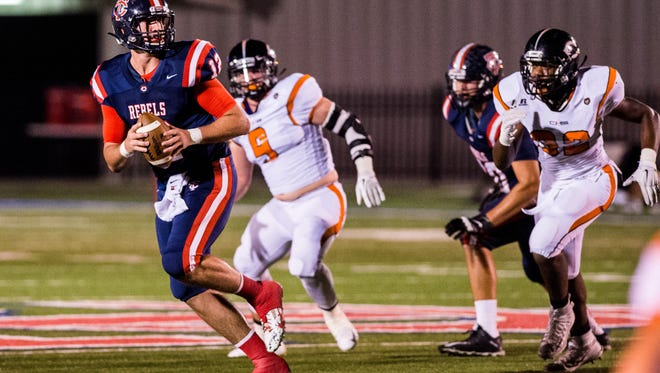 Teurlings quarterback Cole Kelley (12) scrambles away from pressure on a pass attempt during an LHSAA football game against Catholic-BR at Teurlings Catholic High School in Lafayette, La., Friday, Oct. 2, 2015.