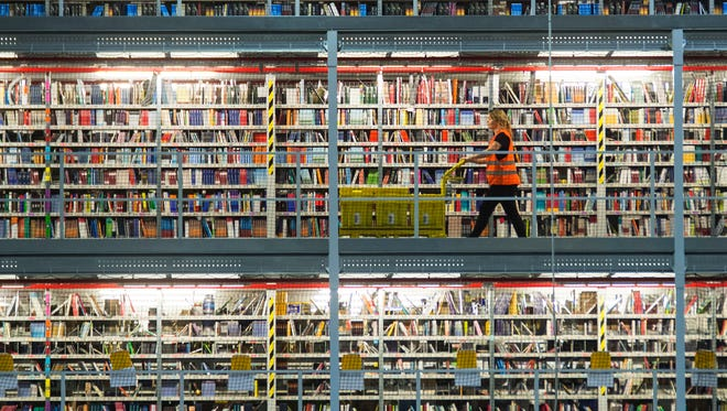 An employee works in the distribution center of the online retailer Amazon during a guided press tour prior to the upcoming Christmas business in Leipzig, central Germany, Thursday, Nov. 19, 2015. Amazon has more than 285 million active customer accounts worldwide. (AP Photo/Jens Meyer)