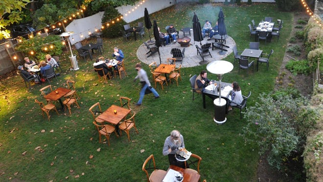 A firepit and socially distant tables highlight the outdoor dining lawn that also serves as a setting for weddings and events at the Winsor House Inn in Duxbury, Friday, Oct. 23, 2020. Tom Gorman/For The Patriot Ledger