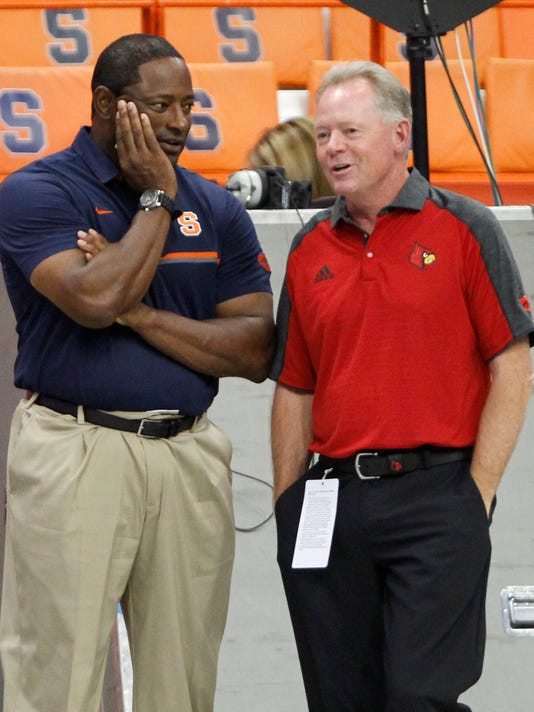 Syracuse head coach Dino Babers, left, and Louisville head coach Bobby Petrino, right, talk before an NCAA college football game in Syracuse, N.Y., Friday, Sept. 9, 2016. (AP Photo/Nick Lisi)