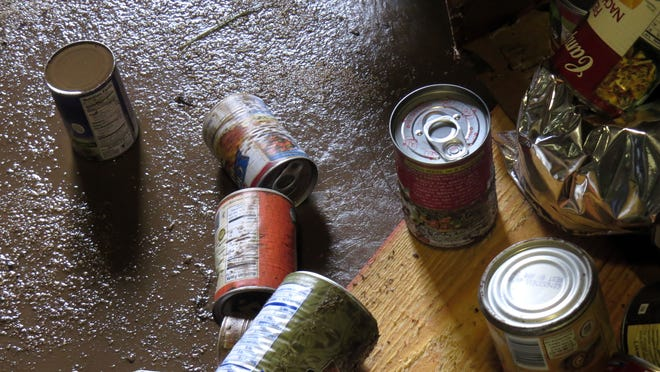 Cans are littered across this section of the Manna Food Pantry warehouse where they were scattered by flood waters.  Most of the food exposed to flood waters and the layers of mud that coat much of the Manna Food Pantry buildings now will have to be destroyed for a variety of health reasons.