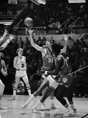 Campy Russell of Michigan throws the ball as he loses his balance while John Laskowski (31) of Indiana makes a vain attempt to catch it during Big 10 playoff game in Champaign, Ill., March 11, 1974. (AP Photo)