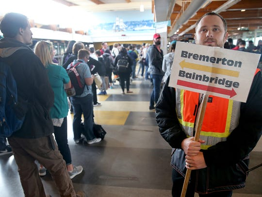 David Gericke of the Washington State Ferries guides passengers at Colman Dock in Seattle.